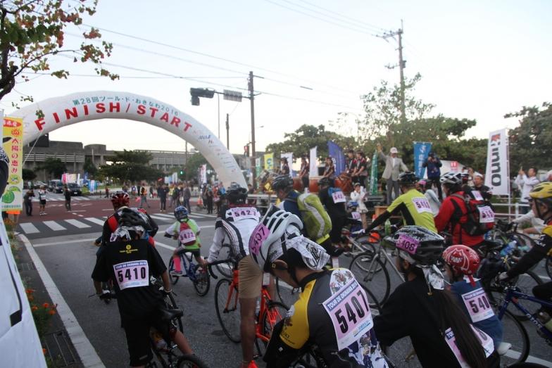 朝7時、名護市屋内運動場前のスタートゲート。まずは伊江島サイクリングの参加者が、和太鼓演奏に見送られながら出発していく。