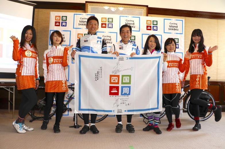 四国一周のフラッグを持って、中村時広・愛媛県知事(中央)、門田基志選手(中央左)、一青妙(ひととたえ)さん(中央右)、ノッてる!ガールズEHIMEのメンバーで記念撮影