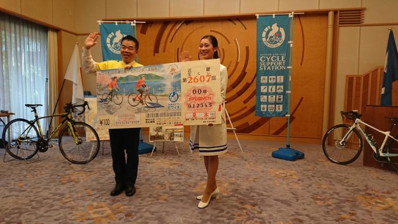 「幸運の女神」谷山美香さんが、ビワイチくじの特大パネルで三日月知事に発売を報告
