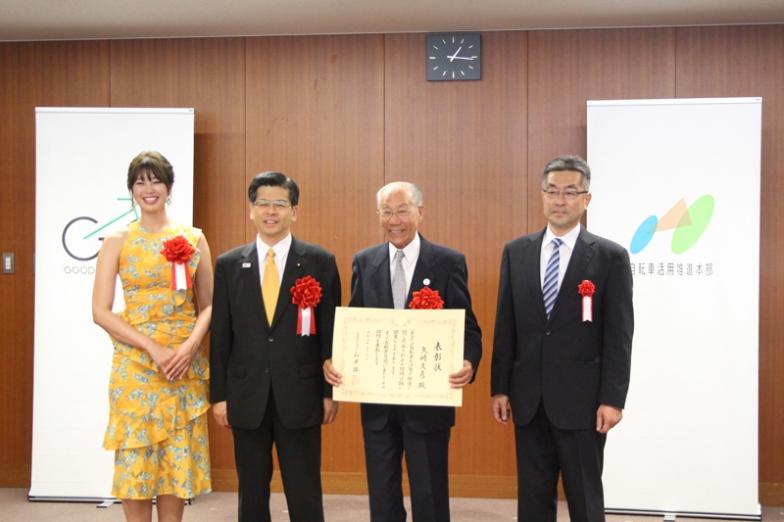 表彰状を持つ矢崎さん。98歳にして現役のサイクリストで、東京葛飾バイコロジー協会を設立し、自転車の安全利用や普及促進に尽力。年齢を聞いて石井大臣は驚いていた