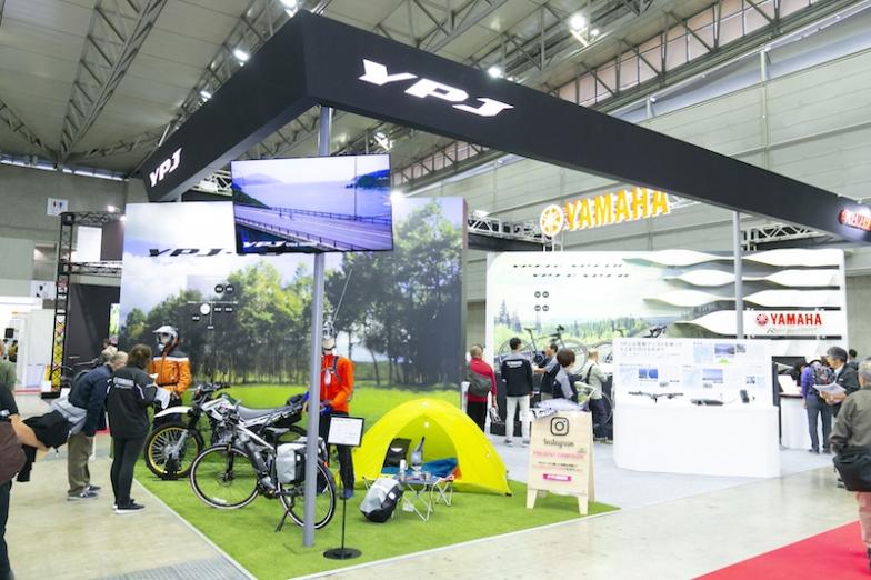 ヤマハブースの手前に展示される「YPJ-TC」。その奥には同社の超人気モーターサイクル・セローの姿も