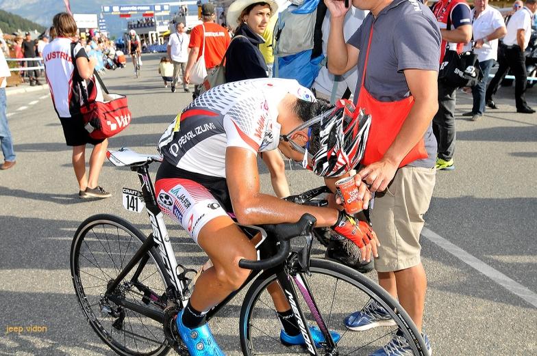 大会最初の山岳ステージを全力で闘い、フィニッシュ後にハンドルに崩れ落ちる雨澤毅明。「疲れと悔しさの両方」でしばらく動けなかった