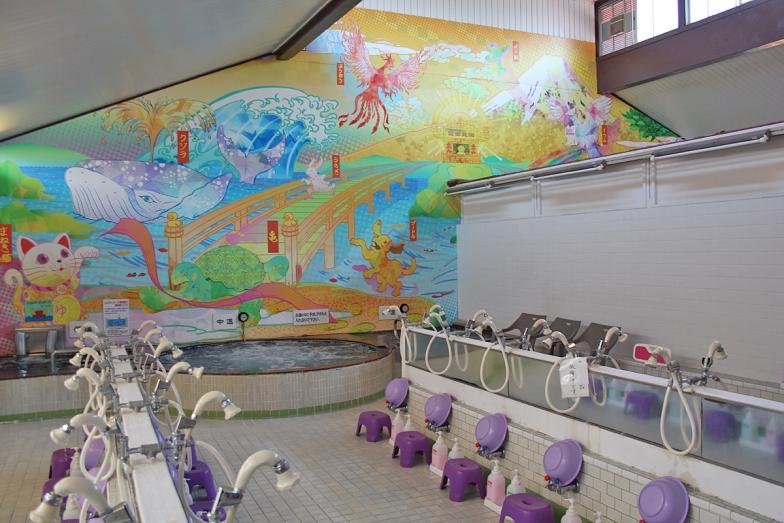 浴室内観。広い洗い場の奥には高温・中温・低温の湯船が並び、彩り豊かな銭湯絵を楽しめる