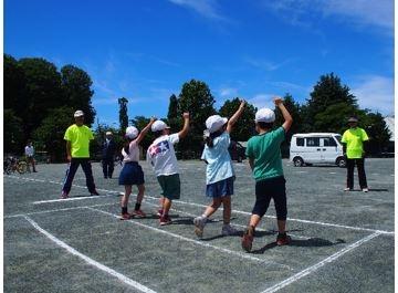 手を挙げて横断歩道の渡り方を学ぶ児童の様子