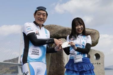 愛媛県の中村時広知事(左)から上野里佳さん(ノッてる!ガールズEHIMEメンバー)に記念品のヘッドスペーサー贈呈