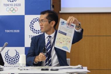 東京2020組織委のスポークパーソン、高谷正哲さん。手に持っているのはロードレースを初めてみる人のためにコースや見どころ、観戦マナーが書かれたチラシ。イベントのホームページからダウンロードできる