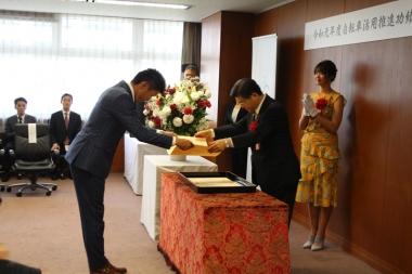 石井国土交通大臣(右)から表彰状を受け取る門田さん。大臣の後ろには自転車アンバサダーの稲村さん。