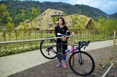 たねやグループ社会部部長の小玉恵さん。八幡山で取れた竹で作ったバイクラックとともに
