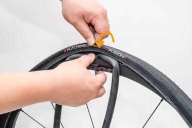 【B】タイヤを手でつまんでバルブの根本部分をまたがせるようにする