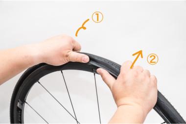【B】①片方の手でタイヤを抑えつつ、②もう片方の手でタイヤを上に押してやる