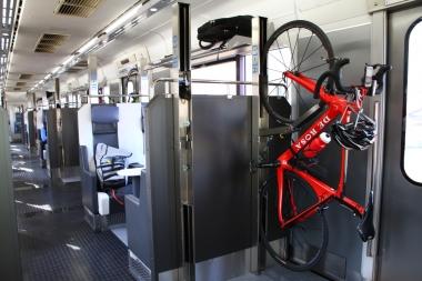 バイクを縦にしてフロントホイールをラックにかけ、ダウンチューブをベルトで固定する