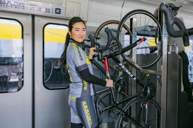 自転車を専用ラックに固定するには、自転車を立ててフロントホイールをラックにかけ、ダウンチューブをタイラップで固定する