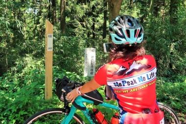 峠の標識を集めるのが趣味だという岡村さん Photo:サイクルスポーツ編集部