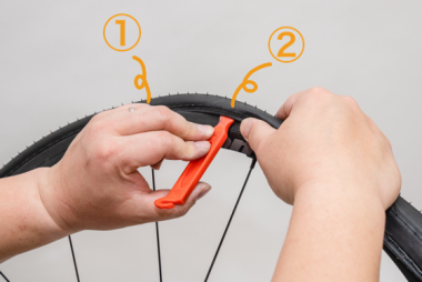ビードがはまっている位置(①)から3〜5cmほどのところ(②)に裏返しにしたタイヤレバーを差し込む