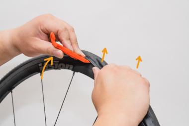①タイヤレバーを引き起こしつつ、②もう片方の手でタイヤを上に押し上げる