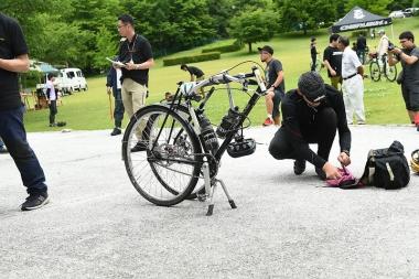 ダブルレッグスタンドで立つ自転車から前輪とともにフォークが抜かれ、小物を使って後輪の真横にセットされる。さらにハンドルステムがピラーと結合するに至って審判の開いた口が……スゴイ