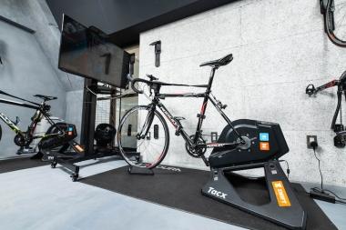 ズイフトに接続されたタックスの最上位モデル。バイクはフレームサイズ別に3台用意されている。部屋は冷房がよく効いているだけでなく、前に扇風機も装備